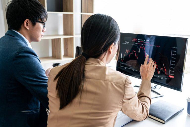 acionistas - duas pessoas acompanhando dados em um computador