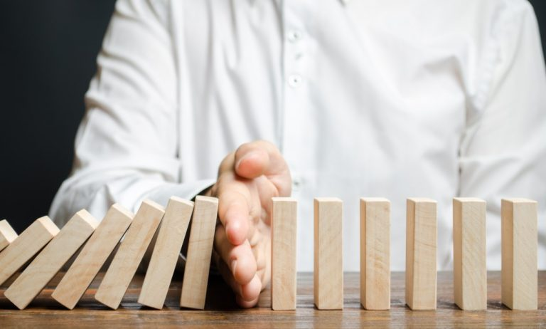 Recuperação judicial - pessoa evitando que dominós caiam