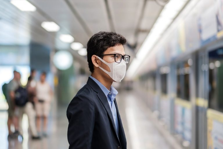 Covid-19 como acidente de trabalho - homem de máscara esperando trem